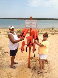 Ron Fields and Debbie Felgenhauer filling the life jacket holders at the beach/swim area near Lake Murray Marina.